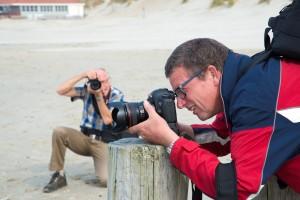 Twee heren zijn aan het fotograferen op het strand van Ameland tijdens het Fotoweekend Ameland. Tekst en Fotografie.