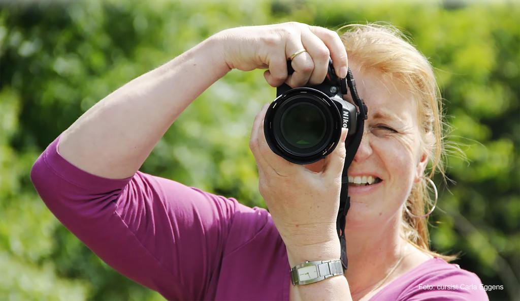 Vrouw met de camera voor het oog tijdens de basiscursus Fotografie.